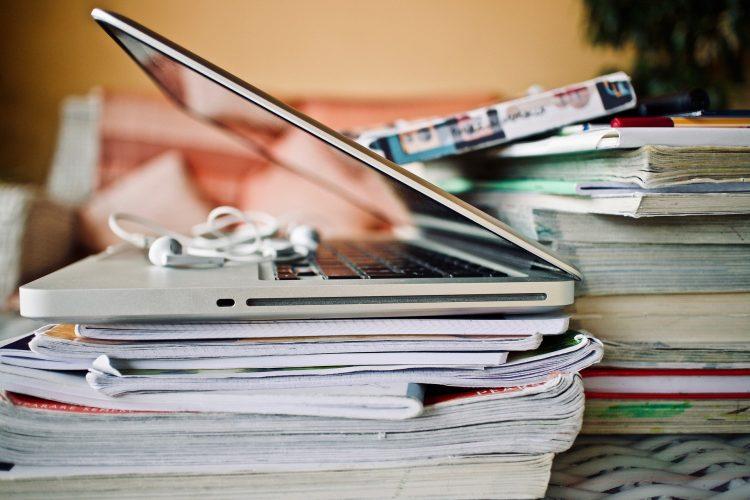 Man sieht zwei große Stapel Bücher. Darauf sieht man einen Laptop und Kopfhörer.